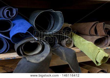 Rolls of unused leather sit on a bookbinders shelf.