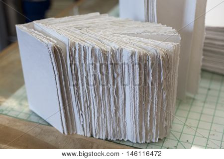 Newly folded paper pages sit at workstation.
