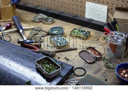 Copper buttons and various tools at a bookbinders desk.