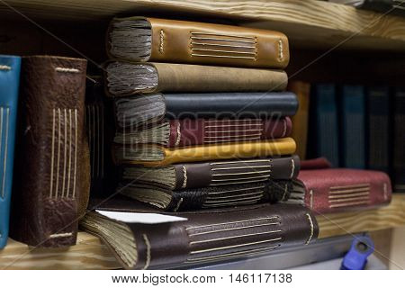 A stack of newly bound book sit on shelf.