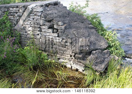 An eroded brick wall at the rivers edge.