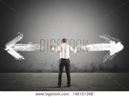 Businessman in front of a choice with arrows in opposite directions