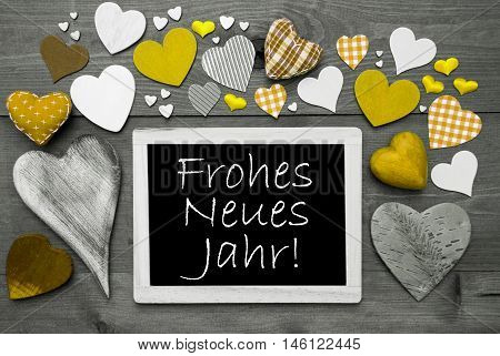 Chalkboard With German Text Frohes Neues Jahr Means Happy New Year. Many Yellow Textile Hearts. Grey Wooden Background With Vintage, Rustic Or Retro Style. Black And White Style With Colored Hot Spots