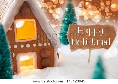 Gingerbread House In Snowy Scenery As Christmas Decoration. Christmas Trees And Candlelight For Romantic Atmosphere. Bronze And Orange Background With Bokeh Effect. English Text Happy Holidays