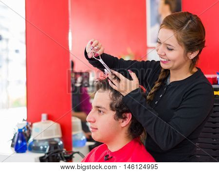 Hairstylist cutting a man hair inside a barbershop with scissors.