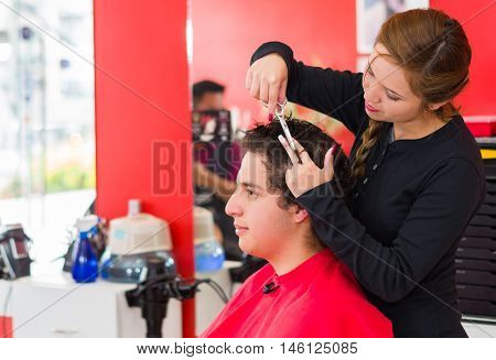 Latin man with curly hair inside a barber shop, nice hairstylist with scissors is cutting his hair.