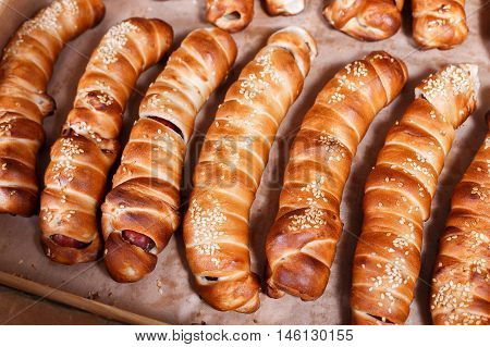 Hot Dog With Sesame Seeds On Shelf In Bakery Shop. Pastries And Bread In A Bakery