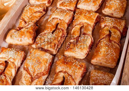 Delicious Puff Pastry With Cheese Filling And Sesame Seeds On Shelf In Bakery Shop. Pastries And Bre