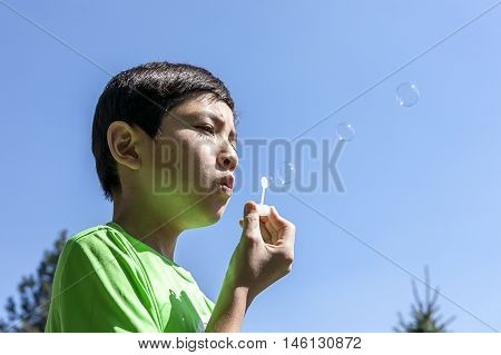 Boy blows small bubbles. A young boy blowing bubbles with a toy.