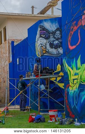 PUNTA DEL ESTE, URUGUAY - MAY 06, 2016: young artist resting in a scaffold while some other friend keep painting the wall.