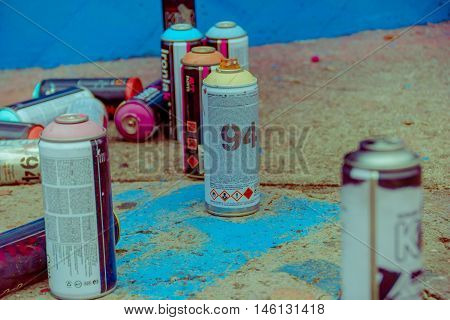 PUNTA DEL ESTE, URUGUAY - MAY 06, 2016: spray cans standing next to a wall while the artist pain a grafitti.