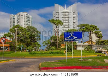 PUNTA DEL ESTE, URUGUAY - MAY 06, 2016: nice street with some trees in the sidewalks and some modern buildings as background.