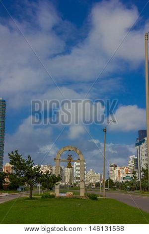 PUNTA DEL ESTE, URUGUAY - MAY 06, 2016: nice street with a monument in the middle sidewalk, some modern buildings as background.