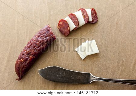 Sliced cheese and jerky. A close up of slices of jerky and squares of provolone cheese.