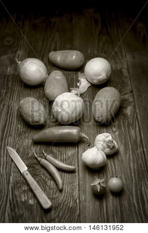 B&W of veggies and a knife on wood.