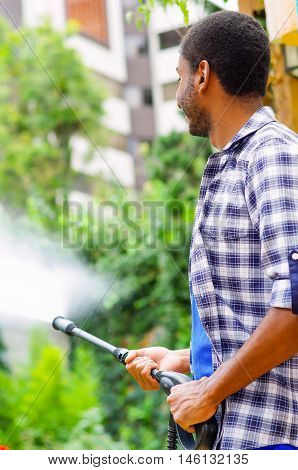 Man wearing square pattern blue and white shirt holding high pressure water gun, pointing liquid to green garden.