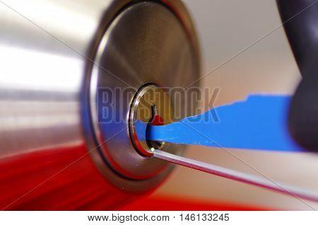 Closeup hands of locksmith using pick tools to open locked door.