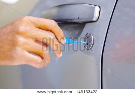 Closeup hands of locksmith using pick tools to open locked car door.
