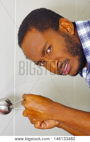 Closeup head and hands of locksmith using pick tools to open locked door, looking at camera with frustrated facial expression.