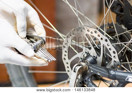 Closeup hand wearing white glove holding multi unbrako key tool next to parts of bicycle wheel, mechanical repair concept,