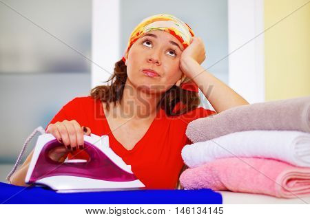 Young charming woman wearing colorful headscarf ironing clothes while daydreaming looking into unknown, laundry housework concept.