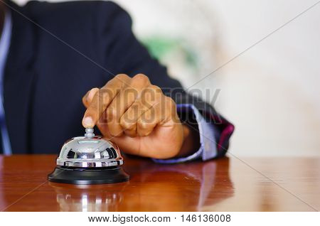 Closeup arm of man wearing blue suit pressing desk bell at hotel reception.