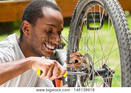 Man wearing white shirt happy working on repairing bicycle mechanics using screwdriver tool.