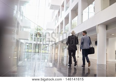 Rear View Of Businessmen Walking Through Office Lobby