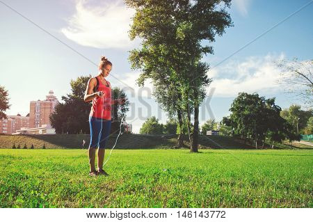 Young Woman Jumping On Rope In A City Park On The Grass