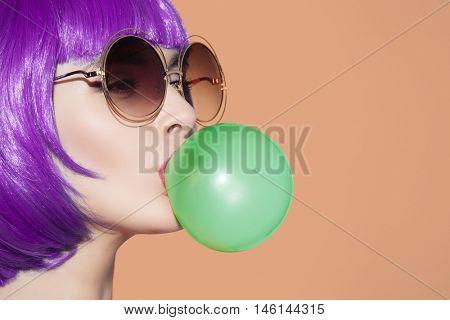 Pop art woman portrait wearing purple wig. Blow a blue bubble chewing gum. Orange background.