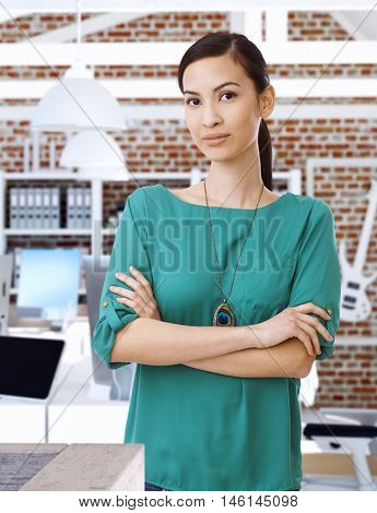 Portrait of confident Asian businesswoman standing arms crossed.