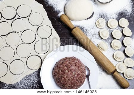 Top view filling dumplings mold with minced meat. Rolling pin near. Step by step guide cooking ravioli or pelmeny