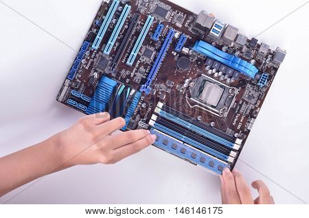 computer motherboard isolated in white background with a person hand placing an equipment into the motherboard
