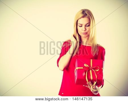 Occasions gifts people concept. Beautiful woman with red gift. Young blonde lady wearing nice outfit dress. Present has the same colour.