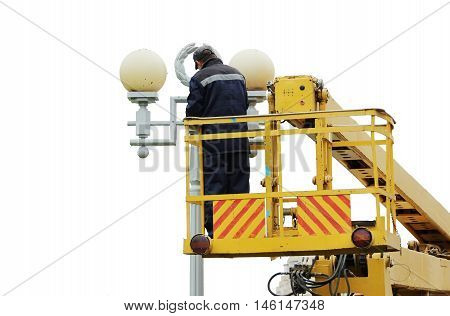 Isolated Electrical worker repairing the wires on the pole with the help of the lift car