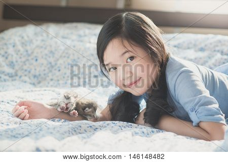Beautiful asian girl lying on a bed with newborn American Short hair kittens