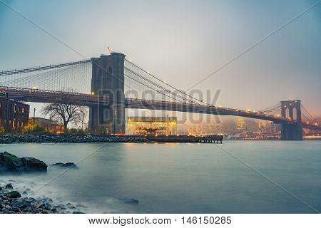 Brooklyn bridge and Manhattan at foggy evening, New York City