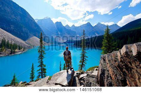 Man hiker on cliff over blue alpine lake. Moraine Lake. Banff National Park. Rocky Mountains. Alberta. Canada.