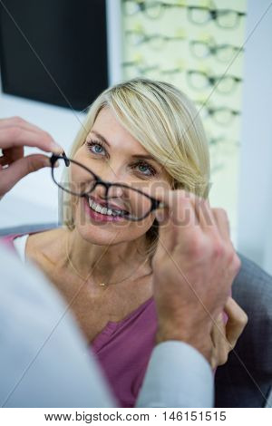 Optician consulting a customer about spectacles and frames in optical store