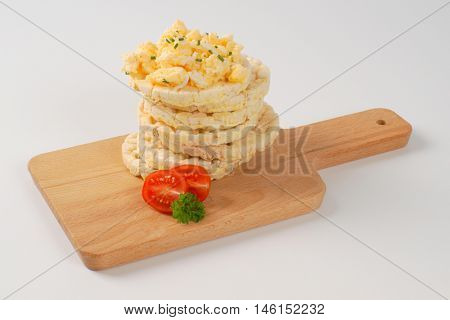 slices of puffed rice bread with scrambled eggs on wooden cutting board