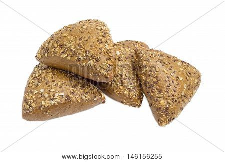 Several small multigrain triangular shaped bread sprinkled with whole sunflower seeds flax and sesame seeds on a light background