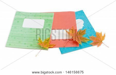 Several school exercise book with covers of different colours and several yellowed maple leaves on a light background