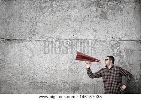 Hipster man shout in trumpet