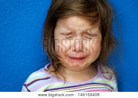 A little girl whose Chicken Pox are just starting to show stands crying her eyes out. She looks so sad with tight clenched eyes spouting tears.