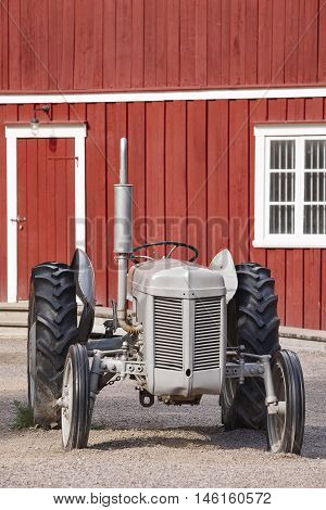 Antique tractor and old red farm facade. Agriculture rural farming. Vertical