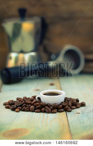 white cup of coffee drink or beverage with roasted brown beans near pot and kettle on wooden table on blurred or defocused background