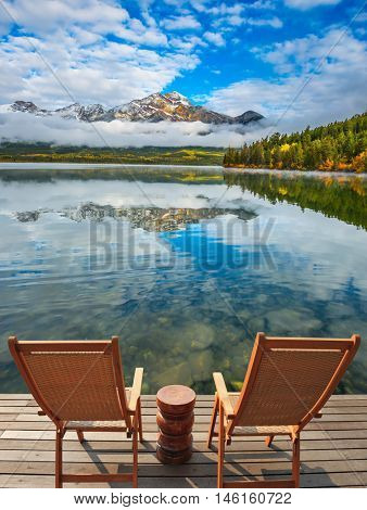 Two deck chairs on a wooden platform.  Pyramid Mountain, Jasper National Park. Concept of  vacation and tourism
