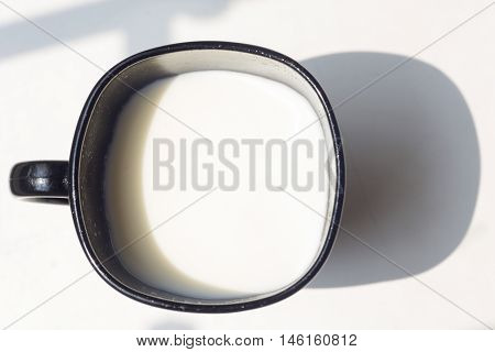 black cup of milk and spoon on natural white background top view