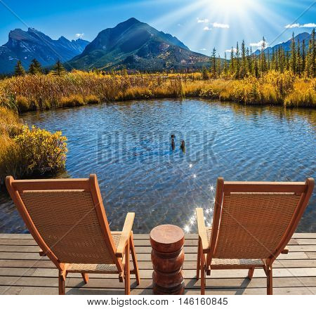 Two comfortable wooden chairs and a small round table on the lake. Indian summer in the Rocky Mountains of Canada. Concept of ecological tourism