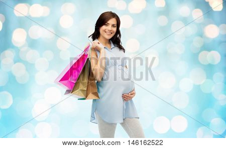pregnancy, sale, motherhood, people and expectation concept - happy pregnant woman with shopping bags touching her big belly over blue holidays lights background
